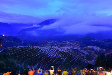 People take pictures of thousands of torches placed in terraced fields during a local festival praying for good harvest at Guilin