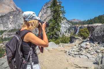 Travel photographer with professional camera takes shot of popular Nevada Falls on Merced River in Yosemite National Park. Woman mountain hiker in Yosemite waterfalls summit overlook, California, USA.