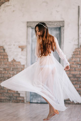 Morning of the bride. Beautiful young woman in elegant white robe walking. Dress developing in the wind. Happy lady in a wedding attire is spinning, boudoir photography
