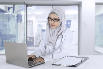 Muslim general doctor works with laptop