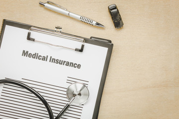 Top view medical insurance form with stethoscope,car on wooden background.