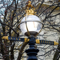 A lamppost in Northcote, Victoria, Australia featuring a glass dome light, and High Street name in gold lettering. Also featuring a golden Queen Elizabeth crown on top.