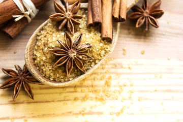 Spices and herbs. Food and cuisine ingredients. Cinnamon sticks, anise stars,  cane sugar on textured background