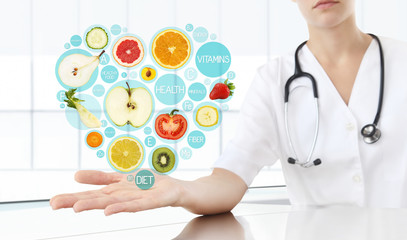 healthy food supplements concept, Hand of nutritionist doctor showing symbols fruits in hearth shape