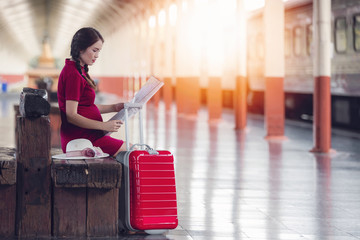 Asian pregnant woman holding map sitting on the wooden bench at railway station