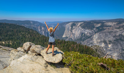 Hiking woman freedom in Yosemite National Park at Sentinel Dome summit. Cheering happy hiker enjoying view of popular El Capitan from Sentinel Dome. Summer travel holidays in California, United States