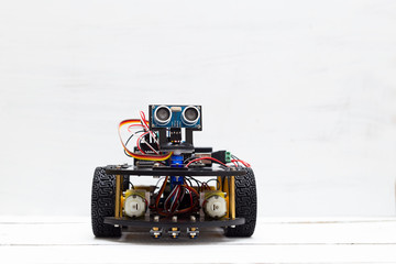 A riding robot on four yellow wheels on a light background