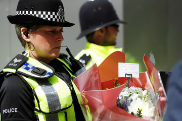 A police officer carries a bunch of flowers with a message of sympathy near Borough Market after an attack left 7 people dead and dozens injured in London