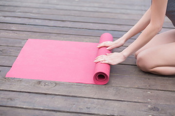 Young yoga Woman rolling her lilac mat