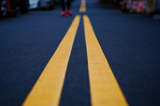 Yellow road line on black street