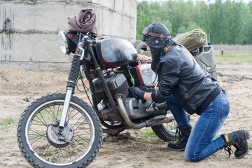 A post apocalyptic woman near motorcycle near the destroyed building