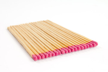 Row of several matches with rose match heads on white background