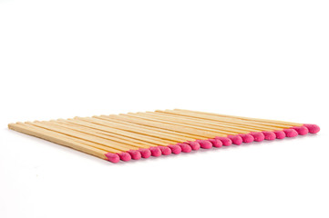 Row of twenty matches with rose match heads on white background