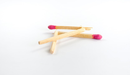 Two broken big matches with rose match head on white background