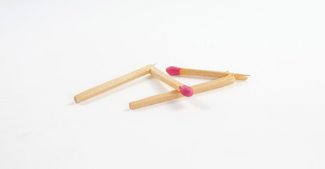 Two broken matches with rose match head on white background