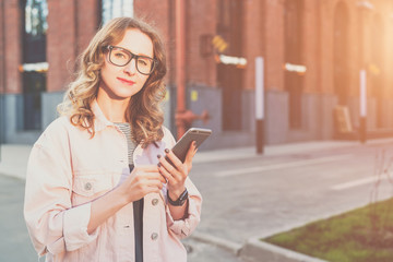 Portrait of young woman in glasses standing outdoors and using smartphone.