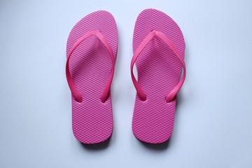 Des paires de chaussures de plage tong en couleurs sur fond blanc