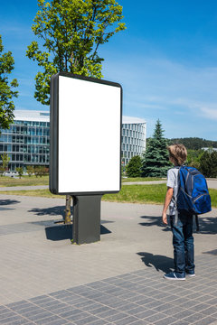 Mock up. Child looking at blank billboard outdoors, outdoor advertising, public information board in the street.
