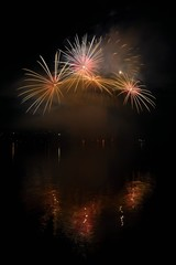 Beautiful colorful fireworks on the water surface with a clean black background. Fun festival and international contest of Firefighters.
