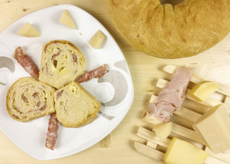 savory cake with salami, ham and cheese on wooden background - top view