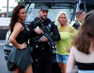 An armed policeman poses for a photograph with music fans before the One Love Manchester concert