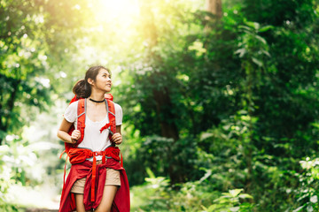 Happy Asian woman traveler with backpack walking in forest.Adventure, travel people concept