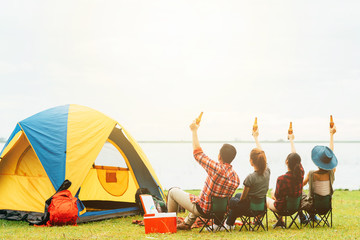 Back view of best friends raised arm with bottle of beer to celebrate while camping during travel.Friendship concept.