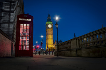 Traditional red phone booth or telephone box with the Big Ben in the background, possible the most famous English landmark, at night in London, England, UK