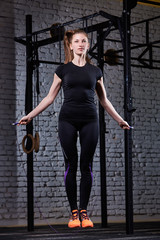 Young beautiful sporty woman working with jumping rope in cross fit gym against brick wall.