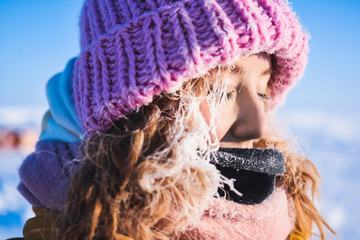 Close-up of a girl in a yellow down jacket pink knitted cap with red hair beautiful young hair in a hoarfrost in the background of the camp Barneo on a snowy north pole in winter