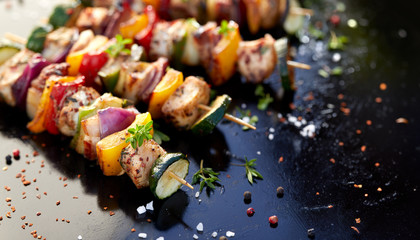 Aluminium Prints Grill / Barbecue Grilled skewers of meats and vegetables on dark background
