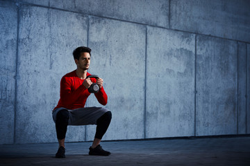 Athletic man doing kettlebell squats