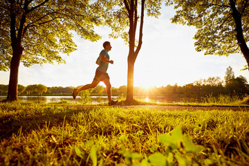 Young man running in park during sunset
