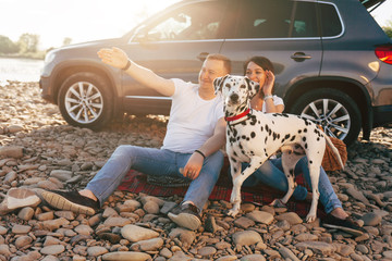 Portrait of happy young adult couple with dog on roadtrip. Man sitting on plaid with woman. Outdoor picnic concept.