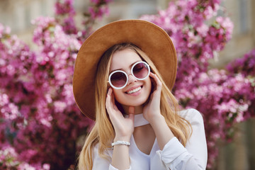 Wall Mural - Outdoor close up portrait of young beautiful happy, smiling woman wearing stylish round sunglasses, yellow hat. Model looking at camera, posing in street, near blooming flowers. Female fashion concept