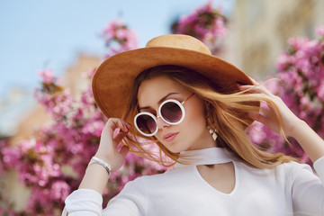 Wall Mural - Outdoor close up portrait of young beautiful girl posing in street, near blooming tree. Model looking  down, wearing stylish white shirt, round sunglasses, yellow suede hat. Female fashion concept