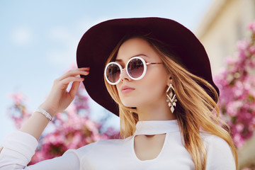Outdoor close up portrait of young beautiful girl posing in street, near blooming tree. Model wearing stylish round sunglasses, wide-brimmed hat, white shirt. City lifestyle. Female fashion concept.