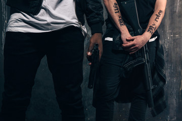 Group of unrecognizable criminals with guns. Armed gangsters with tattoo on dark background. Outlaw, ghetto, murderer, robbery concept