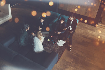 Startup team. Meeting on the couch. Big open space office. Five people. Intentional lens flares