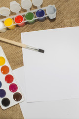 Set of watercolor paints, brushes for painting and blank white paper sheet of sketchbook.
