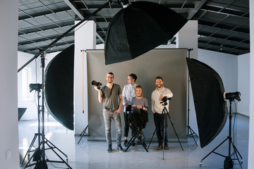 Creative team posing in photo studio interior. Shot of art people looking at camera at the screen. End of hard work , photo for memory, friendship, crew concept