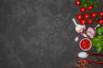 Top view of tomatoes, greens, salt, pepper and garlic on dark vintage background.