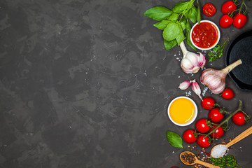 Cooking background. Ingredients and spices for cooking dinner: tomatoes, greens, salt, pepper, garlic. With a frying pan, on a black concrete table. Top view