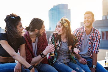 Cheerful young people hanging out on rooftop terrace