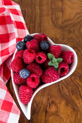 Blueberries and raspberries in the white  dish