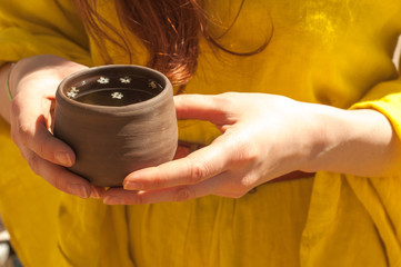 Ceramic mug with elderberry drink in the girl's hands