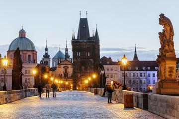 Charles bridge, twilight scenery, street lights visible. Prague iconic travel destination, Czech Republic.