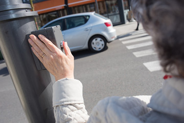 Elderly woman pressing button to cross road