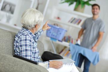 Elderly lady talking to man ironing