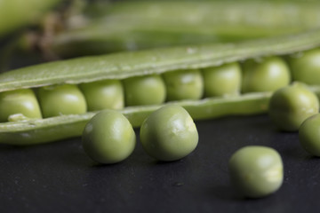 Organic fresh peas on black stone background close up. Healthy diet, vegan and vegetarian concept.
